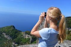 Woman at top of mountain. Looking through binoculars Stock Image