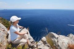 Woman at top of mountain. Looking at sea Stock Photo