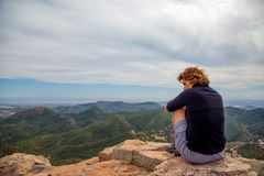 Woman on top of a mountain. Woman relaxes herself on the top of a mountain watching the landscape Stock Photography