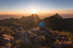 Woman on top of mountain sitting on the rock watching a view landscape at Doi Luang Chiang Dao ChiangMai Thailand. Woman on top of mountain sitting on the rock Stock Photo
