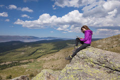 Woman on top of mountain typing in tablet. Sport hiking or trekking woman with purple jacket, sitting on rock peak, typing in digital tablet, next to Lozoya stock photos