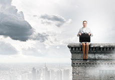 Woman on top. Young pretty businesswoman sitting on top of building high above city Stock Image