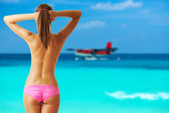 Woman topless on beach with seaplane at Maldives Royalty Free Stock Photography