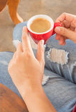 Woman in torn jeans sitting at coffee shop Royalty Free Stock Photo