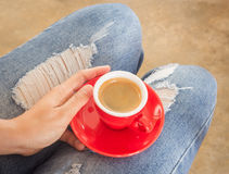 Woman in torn jeans sitting at coffee shop Royalty Free Stock Photos