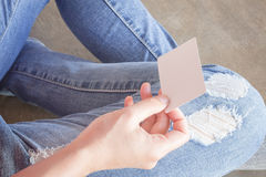 Woman in torn jeans sitting on the ground Stock Image
