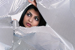 Woman through torn paper. Face of pretty girl with searching eyes looking through torn paper stock photography