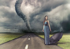 Woman and tornado. Woman,with umbrella on the road and tornado (photo and hand-drawing elements compilation Stock Photos