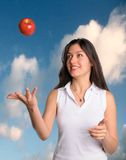 Woman tosses apple in air clouds in background. Beautiful brunette woman tossing an apple in air with blue sky and clouds in background Royalty Free Stock Photography
