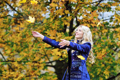 Woman tosses colorful autumn leaves in autumn park Stock Photography