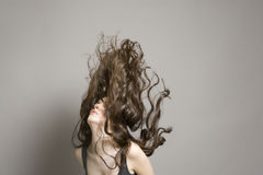Woman Tossing Long Brown Wavy Hair Stock Images