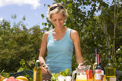 Woman tossing salad on table in garden, smiling, low angle view Stock Photo