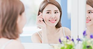 Woman touch her eye. Beauty woman look mirrior happily and touch her eye stock photography