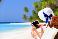 Woman with touch pad on tropical beach Royalty Free Stock Image