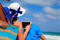 Woman with touch pad on tropical beach Stock Images