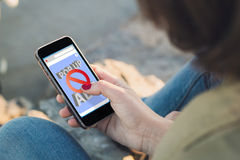 Woman touch the screen of her smartphone with ads blocker on the. Woman holding a smartphone and touching the screen. All screen graphics are made up stock image