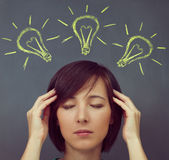Woman touches her head on a background of light bulbs Royalty Free Stock Images