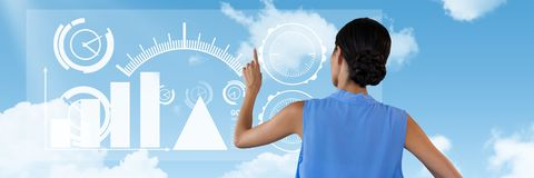 Woman touches interface in sky. Digital composite of Woman touches interface in sky Royalty Free Stock Image