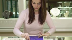 Woman touches necklace at the boutique. Pretty young woman touching necklace at the boutique. Attractive caucasian girl putting chainlet on the little pad Royalty Free Stock Images