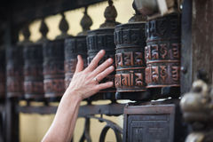 Woman touches praying wheel in nepalese temple Stock Photos