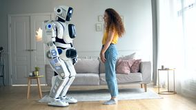 Woman touches a white cyborg. Robot and human cooperation. stock video