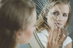Woman touching broken mirror. Beautiful woman with mental disorder touching broken mirror Royalty Free Stock Photography