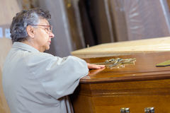 Woman touching coffin in chapel rest Stock Images