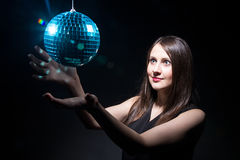 Woman touching disco ball Royalty Free Stock Images