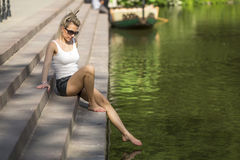 Woman touching a foot of water sitting on a stone embankment. Royalty Free Stock Photos
