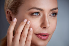 Woman touching her skin. Close up of woman with skin  and looking wrinkles Stock Image