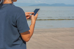 Woman touching her smartphone in hand on the beach. Woman touching her smartphone in hand on the beach with sea, island and blue sky background Stock Photo