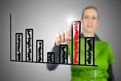 Woman touching the highest column of a bar chart Royalty Free Stock Photos