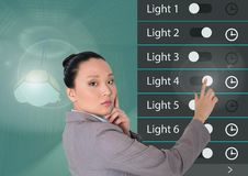 Woman touching Home automation system lighting App Interface. Digital composite of Woman touching Home automation system lighting App Interface royalty free stock photos