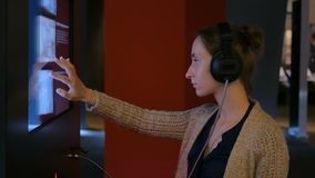 Woman using interactive touchscreen display at modern jewish history museum. Woman touching interactive display, using headphones and listening audio guide at stock footage