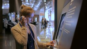 Woman using interactive touchscreen display at modern jewish history museum. Woman touching interactive display, using headphones and listening audio guide at stock video
