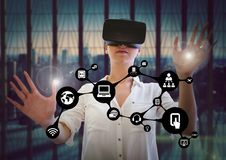 Woman touching interface flare while using virtual reality headset. Against digitally generated background Stock Image