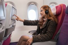 Woman touching LCD entertainment screen on airplane in flight time royalty free stock image
