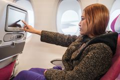Woman touching LCD entertainment screen on airplane in flight time royalty free stock photos