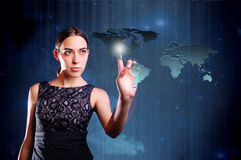 Woman touching map of earth. Attractive young woman touching map of world or planet earth with futuristic background royalty free stock photos