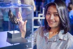 Woman touching moonstone under glass box Royalty Free Stock Photo