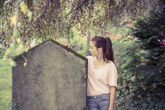 Woman touching a moss overgrown tombstone. Vintage shoot of a woman touching a moss overgrown tombstone Royalty Free Stock Images