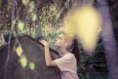Woman touching a moss overgrown tombstone Stock Image
