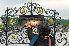 Woman touching the sculpture of Saint Jan Nepomuk on the Charles Stock Image