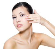 Woman touching  skin on face Stock Images