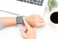 Woman touching smart watch hand on work table Royalty Free Stock Photography