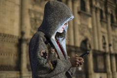 Woman touching smartphone with cathedral in background in w. Woman with hood touching smartphone with cathedral city in background in winter night scene Stock Image