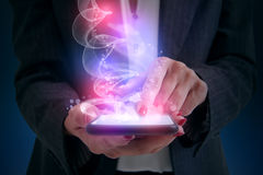 Woman touching smartphone. And shiny magic comes from screen Royalty Free Stock Photography