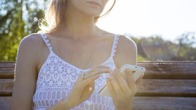 Woman touching smartphone. Young woman touching cell phone Royalty Free Stock Photos
