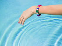Woman touching swimming pool's water surface with fingers Royalty Free Stock Photo