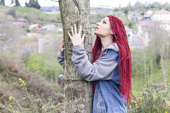 Woman touching a tree, thinking. Redheaded woman touching a tree, thinking, looking up. Concept: Natural environment Royalty Free Stock Photos